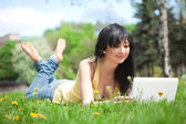 Cute woman with white laptop in the park with dandelions — Stock Photo