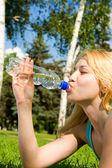 Vacker kvinna dricksvatten på sommaren gläntan — Stockfoto