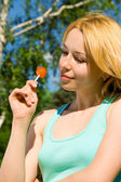 Pretty woman with sweetmeat rest in the park — Stock Photo