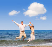 Happy young couple is jumping in the beach — Stock Photo