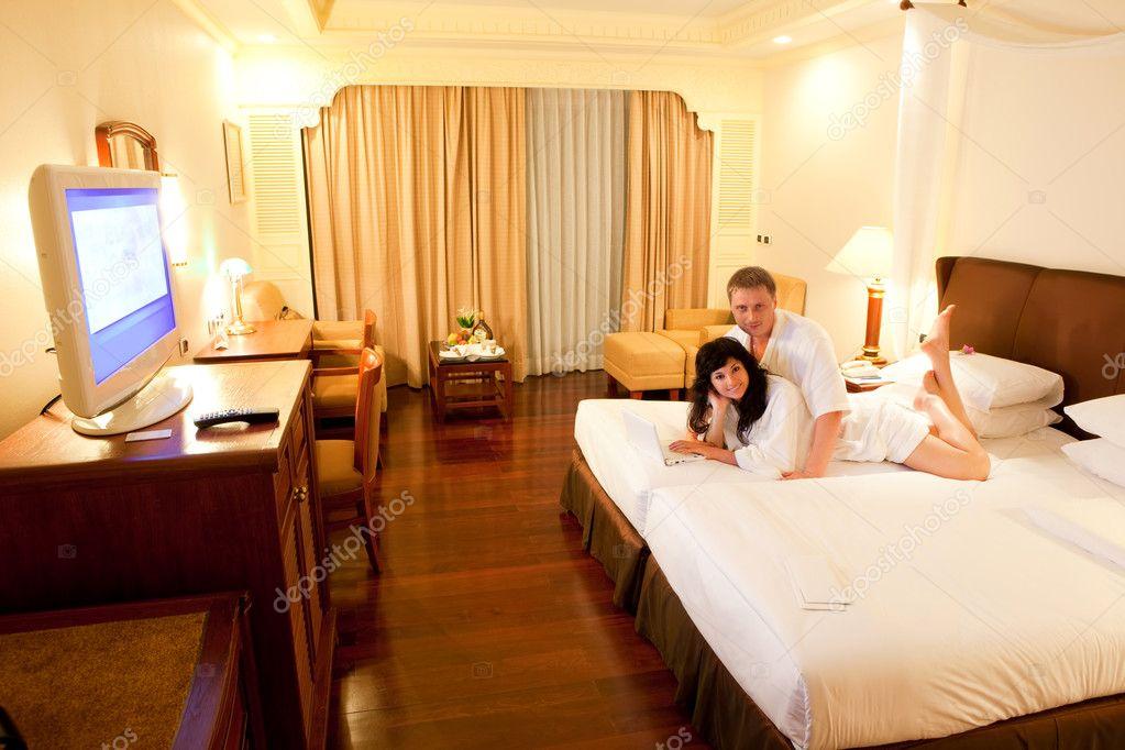 jeune couple avec ordinateur portable blanc couch sur le lit dans la chambre d 39 h tel. Black Bedroom Furniture Sets. Home Design Ideas