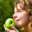 Pretty woman eating green apple on the summer glade — 图库照片