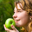 Pretty woman eating green apple on the summer glade — Foto de Stock