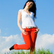 Pretty woman on green grass and sky background — Stock Photo #9426379