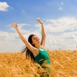 Happy woman jumping in golden wheat — Stock Photo