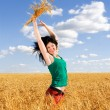Happy woman jumping in golden wheat — Stock Photo #9426505