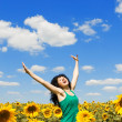 Fun woman jumping in the field of sunflowers — Stock Photo