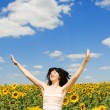 Fun woman jumping in the field of sunflowers — Stock Photo #9426522