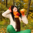 Young pretty woman with tea cup in the autumn park — Stock Photo