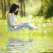 Cute woman with white laptop in the park with dandelions — Stock Photo #9426968