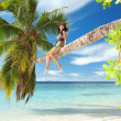 Fashion woman siting upon palm tree on the beach — Stock Photo