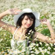 Young happy girl in the daisywheel field - Stock Photo