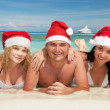 Happy friends in santa hats on the beach — Stock Photo