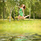 若い赤毛の女性の花の公園でジャンプ — ストック写真