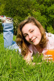 Pretty woman drinking juice on the summer glade — Stock Photo