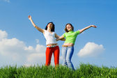 Two happy young women dreams to fly on winds — Stock Photo