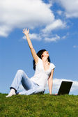 Expressive woman with laptop on the green grass — Stock Photo