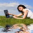 Funny woman with laptop on the green grass - 图库照片