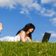 Pretty woman with laptop on the green grass — Stock Photo #9756788