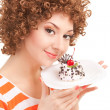Fun woman eating the cake on the white background - Stock Photo