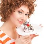 Fun woman eating the cake on the white background — Stock Photo