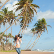 Fashion woman on tropical beach with photo camera - Stock Photo