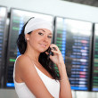 Young pretty woman talking on mobile phone in the airport — Stock Photo