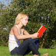 Young blonde reads book in the park — Stock Photo