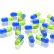 Green and blue pills on white background — Stock Photo