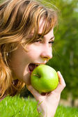 Pretty woman eating green apple on the summer glade — Stock Photo