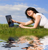 Funny woman with laptop on the green grass — Stock Photo