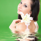 Young woman with lily flower on the green background — Stock Photo