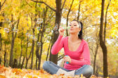 Young woman blowing soap bubble in the autumn park — Stock Photo