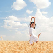 Happy woman jumping in golden wheat — Photo