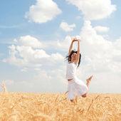 счастливая женщина, прыжки в пшеница золотая — Стоковое фото