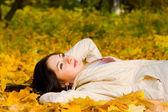 Giovane e bella donna sulla foglia d'autunno — Foto Stock