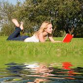 若いブロンドは公園で本を読みます — ストック写真