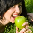 Pretty woman eating green apple on the summer glade - Lizenzfreies Foto