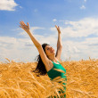 Happy woman jumping in golden wheat — Stock Photo #9864264
