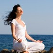Young woman meditation in the beach — Stock Photo #9864325