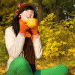 Young pretty woman with cup of tea in the autumn park - Lizenzfreies Foto