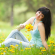 Cute woman in the park with dandelions — Stock Photo #9864751