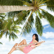Happy woman relaxing in hammock on a tropical beach — Stock Photo #9864954