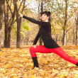 Pretty woman doing yoga exercises in the autumn park — Zdjęcie stockowe