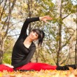 Pretty woman doing yoga exercises in the autumn park — Foto de Stock