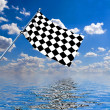 Waving a checkered flag on sky background — Stock Photo #9867617