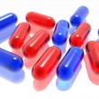 Red and blue pills on white background — Stock Photo