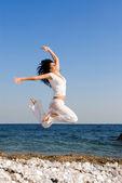 Felice giovane donna sta saltando in spiaggia — Foto Stock