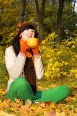 Young pretty woman with cup of tea in the autumn park — Stock Photo