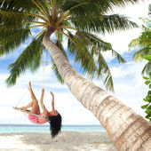 Happy woman relaxing in hammock on a tropical beach — Stock Photo